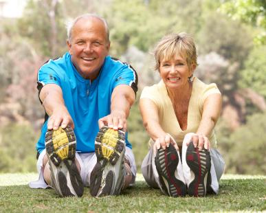 Älteres Paar macht im Park Sport.