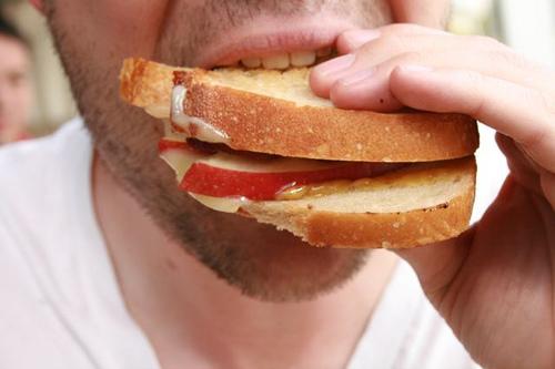 Junger Mann isst belegtes Brot.